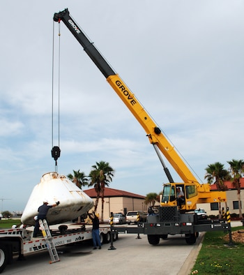 Workers at Patrick Air Force Base, Fla., help guide the 9,000-pound Apollo Boilerplate #1206 onto a flatbed truck for transportation to a local refurbishment facility. On loan here to the Air Force Reserve's 920th Rescue Wing from the Smithsonian Institute's Air and Space Museum, the capsule was once used by Air Force rescue units to train for astronaut recovery during the Apollo and Skylab space programs. (U.S. Air Force photo/Capt. Cathleen Snow)