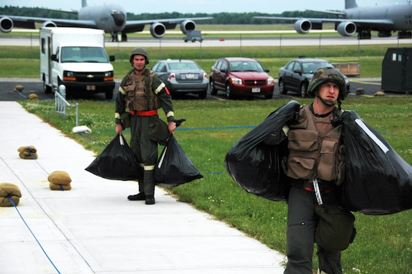 Staff Sgt. James Guldjord (right) and Capt. Scott Meyer carry equipment protected from simulated contamination while waiting for a third crew member during an Operational Readiness Inspection at Volk Field Air National Guard Base, Wis., on June 27.  Both are members of the 18th Air Refueling Squadron, the flying squadron of the 931st Air Refueling Group.  The results of the inspection are scheduled to be announced at an outbrief on July 3 at McConnell AFB. (U.S. Air Force photo/Tech. Sgt. Jason Schaap)