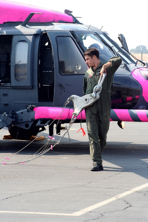 Senior Airman Sean Pellaton, an HH-60G flight engineer from the 129th Rescue Wing, California Air National Guard, pulls a water bucket hoist. The aircrews were training with water buckets, becoming the only crews certified for firefighting suppression duty in the U.S. Air Force and Air National Guard. (U.S. Air Force photo by Master Sgt. Barbara Apkarian)