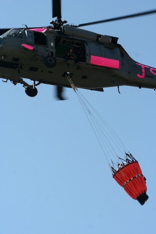 An HH-60G Pave Hawk from the 129th Rescue Wing, California Air National Guard, flies with a water bucket attached near Sacramento, Calif. July 2.  The aircrews were training with water buckets, becoming the only crews certified for firefighting suppression duty in the U.S. Air Force and Air National Guard. (U.S. Air Force photo by Master Sgt. Barbara Apkarian)