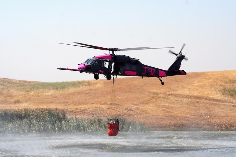 An HH-60G Pave Hawk from the 129th Rescue Wing, California Air National Guard, hovers over a pond near Sacramento, Calif. July 2.  The aircrews were training with water buckets, becoming the only crews certified for firefighting suppression duty in the U.S. Air Force and Air National Guard. (U.S. Air Force photo by Master Sgt. Barbara Apkarian)