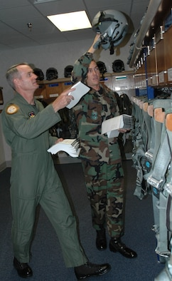 "Col. Darryl Roberson, 325th Fighter Wing commander, assists Senior Airman Adam Turner, 95th Fighter Squadron aviation resource manager, distribute flight publications to pilot lockers. Airman Turner, selected for the Commander's Shadow Program, is responsible for maintaining the Aviation Resource Management System pertaining to aircraft operations, flying hour utilization and pilot training.  ""Airman Turner bleeds Air Force blue and is truly tops amongst his peers,"" said Tech. Sgt. Givonnie Jackson, Airman Turner's supervisor and nominator. Serving the Air Force for eight years, Airman Turner hails from Jacksonville, Fla. (U.S. Air Force photo by Staff Sgt. Timothy Capling)"