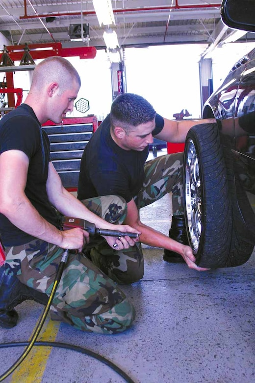 Airman Cory Hickman, and Airman 1st Class Chris Conrad, 552nd Aircraft Maintenance Squadron, replace a tire on a car at the auto shop.  (Air Force photo by Becky Pillifant)