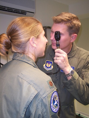 Maj. (Dr.) Mac Dunn, 435th Aerospace Medical Squadron chief of aerospace medicine, performs and eye exam on a patient. (Courtesy Photo)