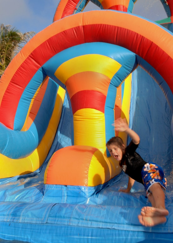 Brenden Paradis slides down the inflatable water slide into a pool or water during Freedom Fest at Arc Light Park here July 3. The water slide was one of many activities for the children to enjoy at Freedom Fest. Freedom Fest is hosted by the 36th Force Support Squadron and held annually to recognize and celebrate our Independence Day. (U.S. Air Force photo by Airman 1st Class Nichelle Griffiths)