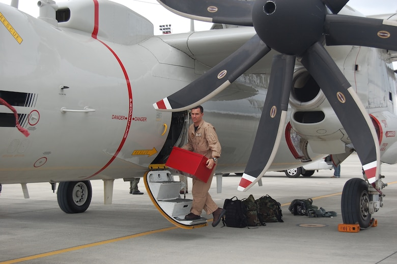 Lieutenant Commander Jerald Rushing, Navy Detachment Operations Officer, offloads equipment from a Navy E-2C Hawkeye on the ramp of Forward Operating Location Manta.  (U.S. Air Force photo/Capt. Ashley Norris)