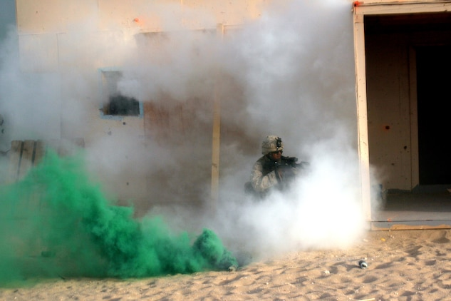 Concealed in smoke during a live-fire, urban-terrain exercise, Lance Cpl. Randy Aisen, a light-armored vehicle scout, provides cover while his team members place a breach charge. Aisen serves with Weapons Company, Battalion Landing Team 2/5, 15th Marine Expeditionary Unit, which came ashore to Kuwait in late June to conduct sustainment training in the north.