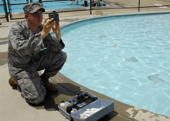 Airman 1st Class Anthony Maffia, 375th Civil Engineer Squadron utility system journeyman, takes samples from the fitness center community pool to check the chlorine and PH levels. The tests are performed three times a day seven days a week to ensure the publice safety.