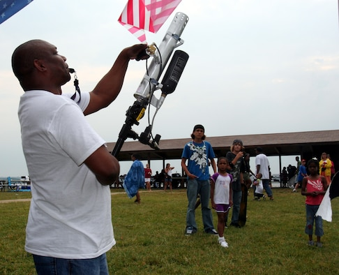 """Donald """"DC"""" Smith, 11th Services Division, uses an air cannon to launch a prize in the crowd July 4 during the 6th Annual Freedom Fest at Bolling Green Park. (U.S. Air Force photo by George Scott)"""