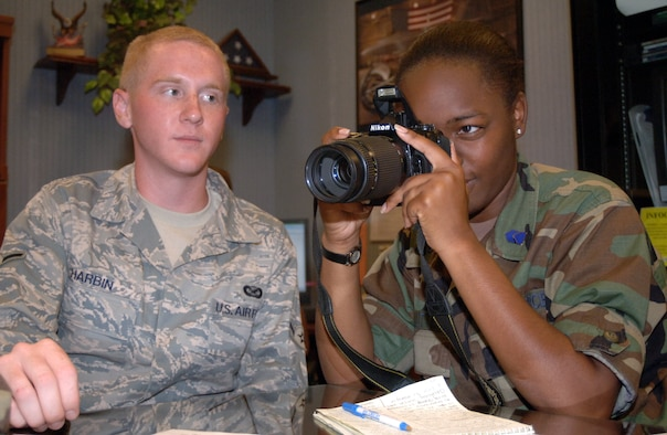 Airman Josh Harbin, 14th Flying Training Wing, shows Candice Dillitte, an Operations Air Force cadet, how to operate a Nikon D100 camera. Cadet Dillitte shadowed the public affairs office during her stay at Columbus AFB for the Operation Noncommissioned Officer Program. (U.S. Air Force photo by Senior Airman Danielle Hill)