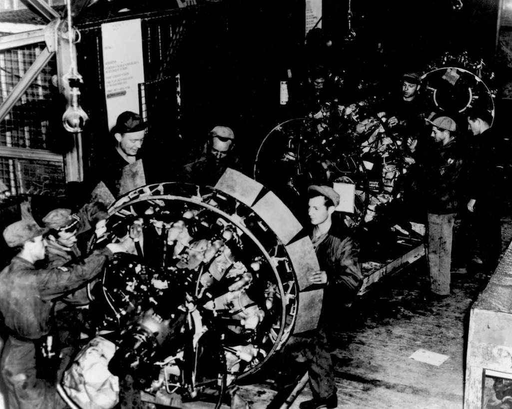 Workers service an engine on the engine buildup line at Rhein Main Air Base, Germany in 1948. Here the engines used on C-54 Skymasters flying the airlift to Berlin were disassembled, checked, worn parts replaced, reassembled and returned to service on the aircraft. (Courtesy photo)