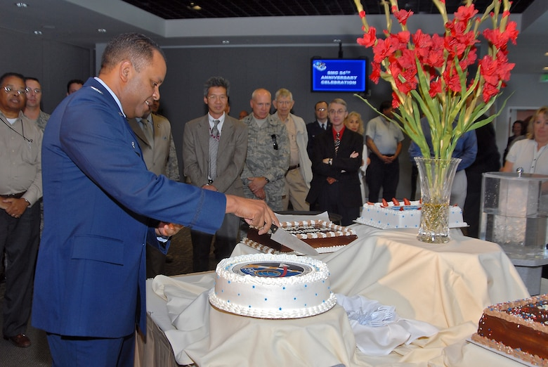 Col. Samuel Greaves, SMC Military Satellite Communications Systems Wing commander, cuts the cake at a ceremony to mark SMC's 54th birthday, July 1. Approximately 200 Los Angeles AFB military and civilian personnel attended the event. (Photo  by Joe Juarez)