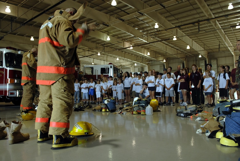 Fire students from the Louis F. Garland Fire Academy demonstrate how to quickly put on the fire fighter uniform for the DEFY youth. The children were given the opportunity to tour the fire school and witnessed first hand what it takes to become a fire fighter. (U.S. Air Force photo by Senior Airman Kamaile Chan)