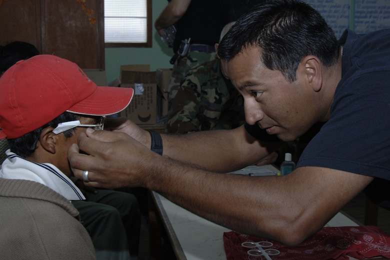 Staff Sgt. Angel Adame, an optometry technician from March Air Reserve Base, Calif., fits a Peruvian man with glasses, June 30, during a medical mission in Chiara, Peru.  The medical mission is part of a larger effort called New Horizons - Peru 2008, a U.S. and Peruvian humanitarian mission that will bring relief to underprivileged Peruvians. (U.S. Air Force Photo/1st Lt. Mary Pekas)