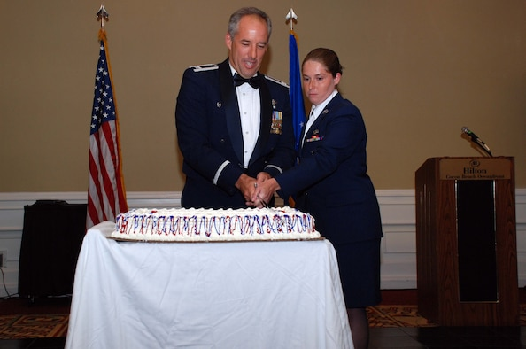 PATRICK AIR FORCE BASE, Fla. - Col. Steven W. Kirkpatrick, commander of the 920th Rescue Wing, get the first bite of the cake at the Wing's third annual military ball during the July Unit Training assembly. Colonel Kirkpatrick is assisted in cutting the cake by Airman Basic Alisha Dixon from the 920th Security Forces Squadron following the Air Force tradtition of having the highest and lowest ranking individuals in the room cut the cake with the ceremonial sword.  (U.S. Air Force photo / Master Sgt. Raymond F. Padgett)
