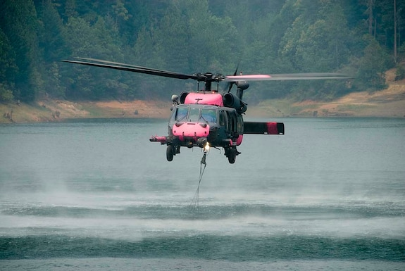 Jolly 92, an HH-60G Pave Hawk from the 129th Rescue Wing, a California Air National Guard unit based out of Moffett Federal Airfield near Mountain View, Calif., performs multiple water bucket missions over Butte County wildfires in California. The wing is the only unit in the Air Force qualified to participate in water bucket drops. There are currently 21 rotary-wing aircraft supporting the California wild fires, nine aircraft from other states. (U.S. Air Force photo by Staff Sgt. Andrew Hughan)
