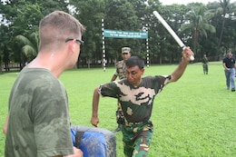 A Bangladeshi Rifles soldier swings his bayonet to suppress a simulated suspect after Marine instructors doused him with oleoresin capsicum (pepper) spray July 14 during Non-Lethal Weapons Executive Seminar 2008 here. The training provides a better understanding of the effects of pepper spray before it is employed.