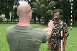 Gunnery Sgt. Dennis Dodd douses a Bangladesh Rifles soldier with oleoresin capsicum (pepper) spray July 14 during Non-Lethal Weapons Executive Seminar 2008 here. The training is designed to understand the effects of pepper spray before deciding to employ it. Dodd is the senior anti-terrorism force protection instructor with III Marine Expeditionary Force's Special Operations Training Group.