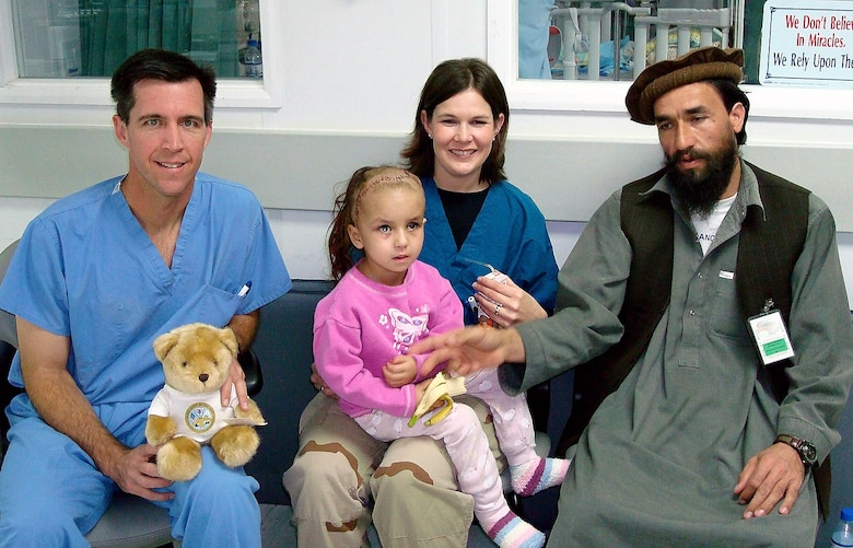 Lt. Col. (Dr.) Randall McCafferty, a neurosurgeon deployed from Lackland Air Force Base, Texas (left); and Capt. Stacy Friesen, a neonatal intensive care nurse deployed from Travis Air Force Base, Calif.; visit with Zahara and her father at the Craig Joint Theater Hospital, Afghanistan. Zahara was injured and received several surgeries at the hospital. (Courtesy photo)