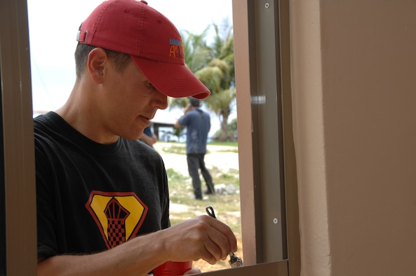 U.S. Air Force Tech. Sgt. Les Neipert of the 36th Operations Support Squadron paints a window sill during a volunteer mission for Habitat for Humanity in Yona July 11.  Habitat for Humanity is a program that provides homes for local families that are in need. The family that will be living in this new house also helped out with the 36th OSS volunteeers. (U.S. Air Force photo by Airman 1st Class Courtney Witt)