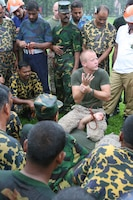Sgt. Wesley Wallace teaches cuffing procedures to Bangladesh service members and local law-enforcement personnel July 15 during Non-Lethal Weapons Executive Seminar 2008 here. Wallace is an anti-terrorism force protection instructor with Maine Corps Base Camp Butler's Provost Marshal's Office.