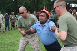 Marine instructors ease Bangladesh Air Force Flight Lt. Muzaffor Raahath to the ground while experiancing the effects of a X26E electro-muscular disrupter (stun gun)  July 15 during Non-Lethal Weapons Executive Seminar 2008 here.