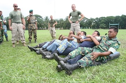 Bangladesh service members and local law-enforcement personnel cringe in pain as they experience the effects of a X26E electro-muscular disrupter (stun gun)  July 15 during Non-Lethal Weapons Executive Seminar 2008 here.