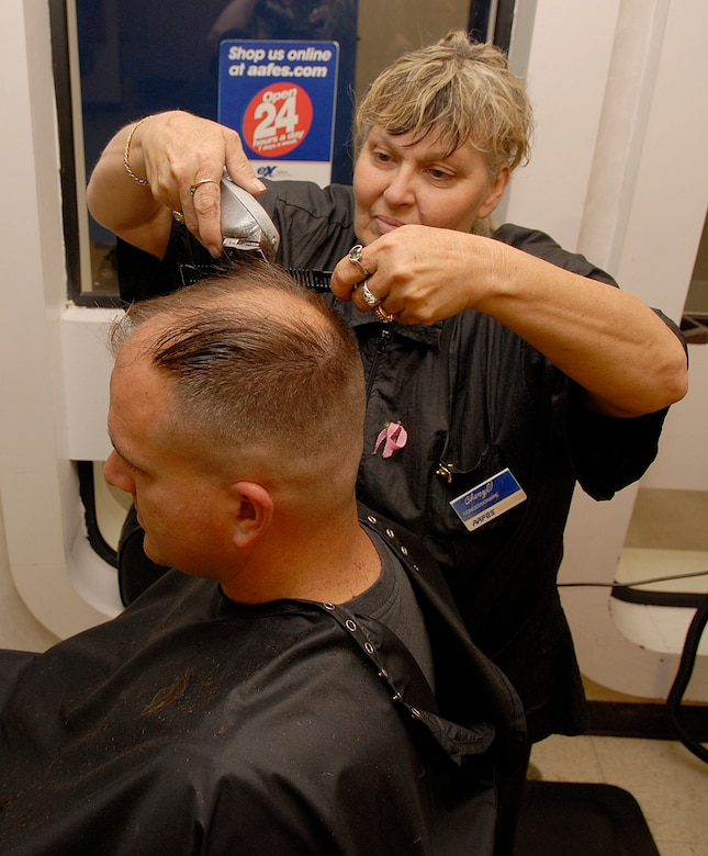 VANDENBERG AIR FORCE BASE, Calif. --  Cheryl Davis, manager of the Vandenberg Barber Shop, gives a haircut to  Staff Sgt. Kristopher Powell, 576th Training Squadron, Monday here.  (U.S. Air Force photo/Airman 1st Class Andrew Satran)