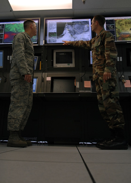 VANDENBERG AIR FORCE BASE, Calif. --  Tech. Sgt. Corey Latiolais, NCO in charge of weather station operations, and Capt. Jonathan Mason, a launch weather officer, both with the 30th Weather Squadron, go over weather data in the operations center here Friday. (U.S. Air Force photo/Airman 1st Class Andrew Satran)