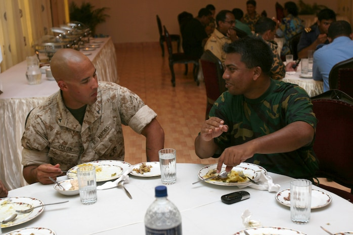 Lance Cpl. Jesus Colone (left) and Bangladesh Army Maj. Shahed Minhazsiddiquei discuss American culture   July 16 during Non-Lethal Weapons Executive Seminar 2008 here. Colone is an amorer with III Marine Expeditionary Force Headquarters Group. Minhazsiddiquei is a weapons instructor with the Bangladesh Army School of Infantry.