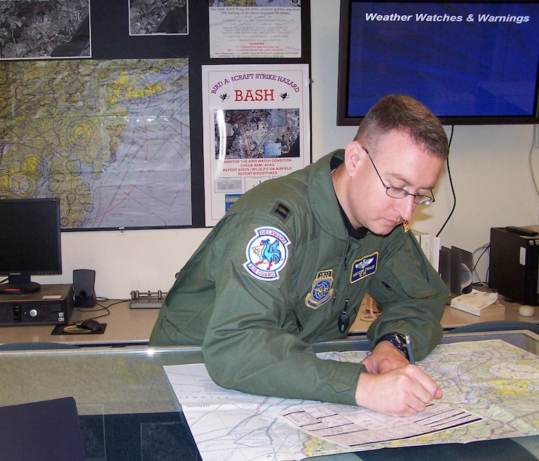 Capt. Chris Strickler, 166th Operations Support Flight, Delaware Air National Guard, the mission planner for the June 7, 2008 five-ship C-130 formation and airdrop mission, documents flight routes in the base operations flight planning room.