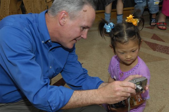 Col. Randall Guthrie shows one of the young patients her picture on his digital camera.