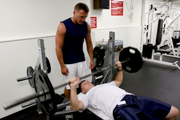 Staff Sgt. Brett Garmon, G-4 air staff noncommissioned officer, U.S. Marine Corps Forces, Pacific, utilizes the bench press and weights, while safely being spotted by Master Sgt. Bill Atwater, G-4 maintenance management chief, MARFORPAC at the  Semper Fit Center here.