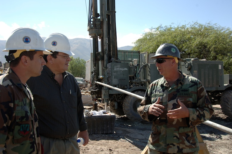 Petty Officer 1st Class Mark Goff, Task Force New Horizons lead driller, explains the Navy Seabee's well-drilling progress at Luricocha, Peru, July 13, to Dr. Luis Cabeña, Chief of Staff to the Peruvian Ministry of Defense.  The Seabees are supporting New Horizons - Peru 2008, a partnered effort between the U.S. and Peru to bring relief to underprivileged Peruvians. (U.S. Air Force Photo/1st Lt. Mary Pekas)