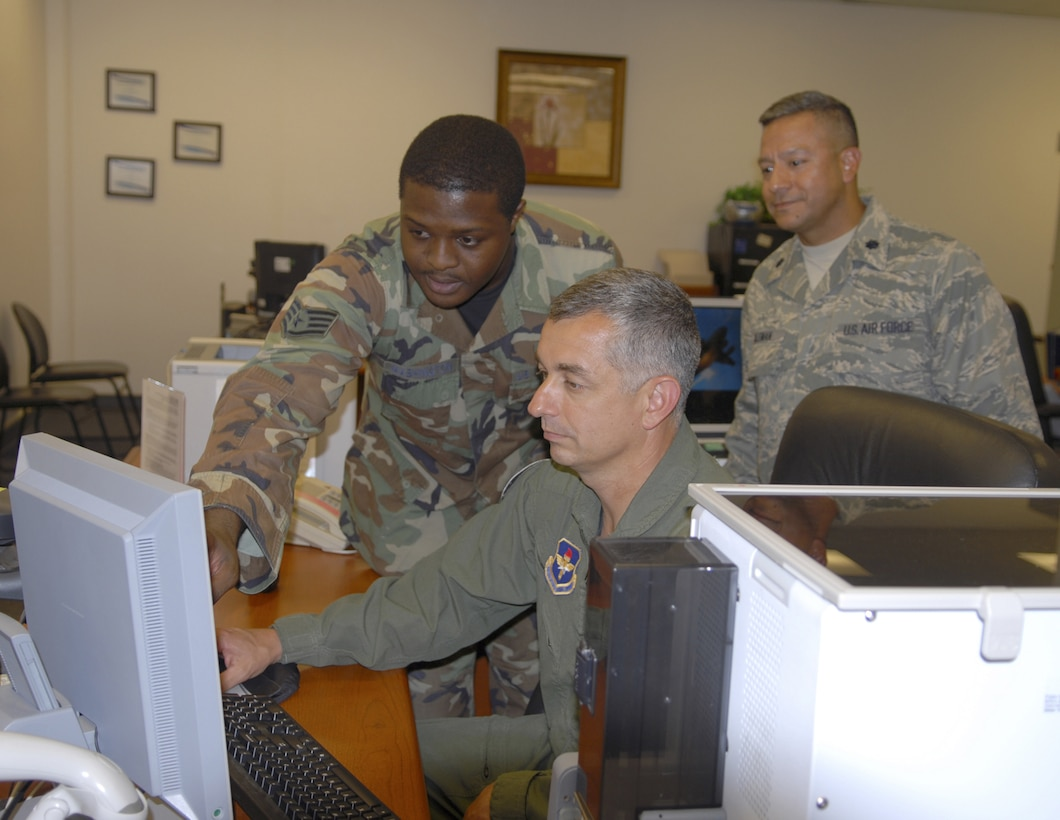 Staff Sgt. Christopher Washington, 14th Force Support Squadron, shows Col. Roger Watkins, 14th Flying Training Wing commander, how to issue a CAC card during his tour of the Military Personnel Flight. (U.S. Air Force photo by Elizabeth Owens)