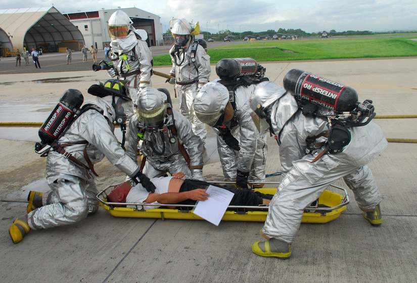 SOTO CANO AIR BASE, Honduras ? Joint Task Force-Bravo fire fighters work to stabilize a simulated victim of a C-21 crash July 10. The fire fighters were charged with the task to put out a simulated fire and rescue the trapped occupants of the simulated plane. The fire fighters were part of a base-wide exercise that simulated a mass casualty, anti-terrorism and force protection scenarios. (U.S. Air Force photo by Staff Sgt. Joel Mease)