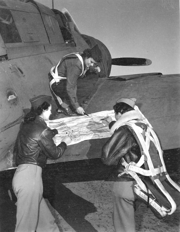 Three WASPs on right wing of A-25 checking the flight plan before a tow mission. (U.S. Air Force photo)