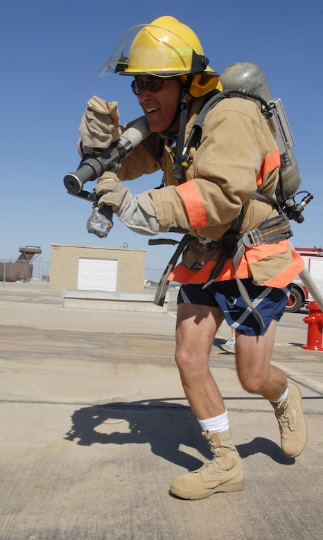 Colonel Barry Simon, 17th Medical Group commander, drags a hose approximately fifty feet where a target awaits the spray of his hose during the Rookie Firefighter Combat Challenge July 18. (U.S. Air FOrce photo by Senior Airman Kamaile Chan)