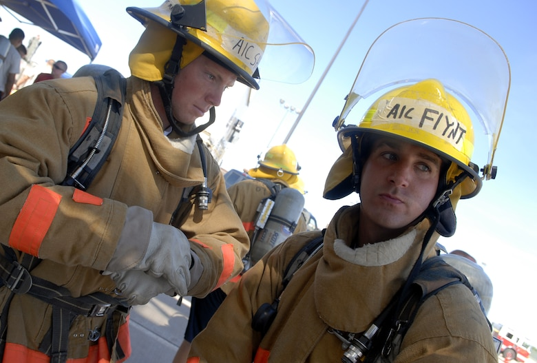 Airmen 1st Class Ryan Shell and Sean Flynt, 312th Training Squadron students, prepare themselves for battle during the Rookie Firefighter Combat Challenge July 12. (U.S. Air FOrce photo by Senior Airman Kamaile Chan)