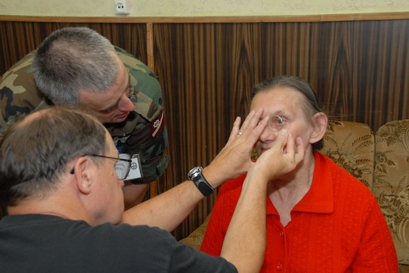 Major Nelson Edwards, an Optometrist with the 127th Wing, Michigan Air National Guard, along with his interpretor, Pvt 1st Class Edgars Godpeteris, from the Latvian National Guard, perform an eye examination at the Alunske Senior Regional Center.