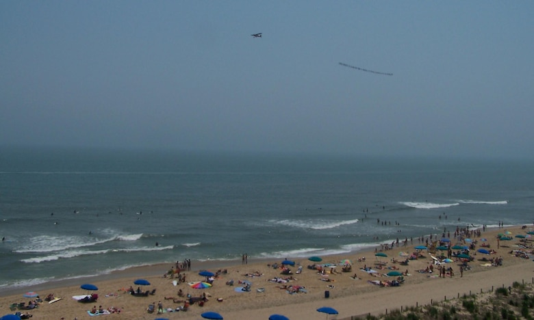 A banner-towing small civilian aircraft owns the sky over Ocean City, Md. shortly before a five-ship large formation of Delaware Air National Guard C-130 transport aircraft from the 166th Airlift Wing in New Castle, Del. flew overhead.  Beachgoers at Md. and Del. coastal areas saw part of the 700-mile, three-hour training flight on June 7, 2008 over four states (Del., Md., Va., and N.J.) culminating in an airdrop over Coyle Field, N.J. and a return to home station at New Castle Airport, Del.