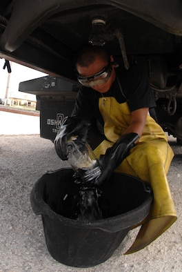 Airman 1st Class John Nguyen drains a quart of jet fuel at a vehicle check station here July 14. A quart of fuel was drained and visually checked for sediments and water before allowing the R-12 to deliver fuel to the flight line. The main purpose for this check is to insure that clean, dry fuel is pumped into the aircrafts. (U.S. Air Force photo by Airman 1st Class Courtney Witt)