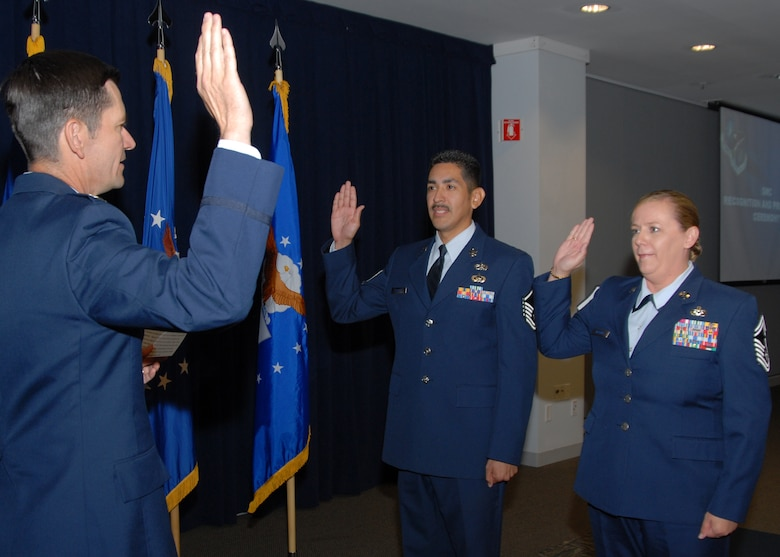 (left to right) Col. Joseph Schwarz, 61st Air Base Wing commander, assists promotee to Master Sergeant, Peter Franco, Space Superiority Systems Wing, and promotee to Senior Master Sergeant, Lori Vrooman, Space and Missile Systems Center Office of the Staff Judge Advocate, reaffirm their Oath of Enlistment during the monthly recognition and promotion ceremony held at the Gordon Conference Center at Los Angeles Air Force Base, June 30.  (Photo by Joseph Juarez)