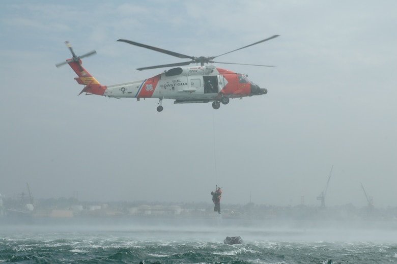 """An MH-60J Coast Guard helicopter piloted by Lt. Jeremy Denning and Lt. John Filipowicz maneuvers so rescue swimmer AST3 Logan Banner can extract Dr. (Lt. Col.) Tom Rotkis from the ocean. Extraction was one part of the water survival training conducted during the July unit training assembly at Naval Amphibious Base Coronado in San Diego. """"It's disorienting out there, and the rotor wash is amazing,"""" said Dr. Rotkis, a flight surgeon at the 162nd Fighter Wing. (Air National Guard photo by 1st Lt. Dan Dodson)"""