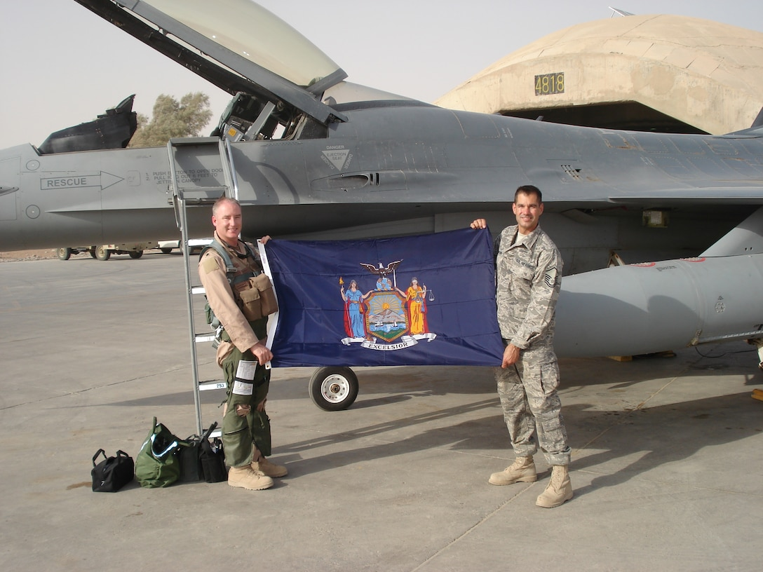 174th Fighter Wing members Lt. Col. Scott Brenton and MSgt. Scott Simpson display a New York State flag that was flown over Iraq during a combat mission.  The flag will be presented to Congressman Jim Walsh by 174th Fighter Wing Commander Col. Kevin W. Bradley upon the unit's return to Hancock Field within the next few weeks.