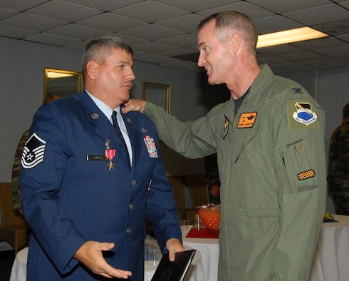 Col. Darryl Roberson, 325th Fighter Wing commander, congratulates Master Sgt. Michael Fowler, 325th Civil Engineer Squadron fire protection specialist, for earning the Bronze Star Medal for meritorious achievement during his time in Afghanistan.  (US Air Force photo by Susan Trahan)