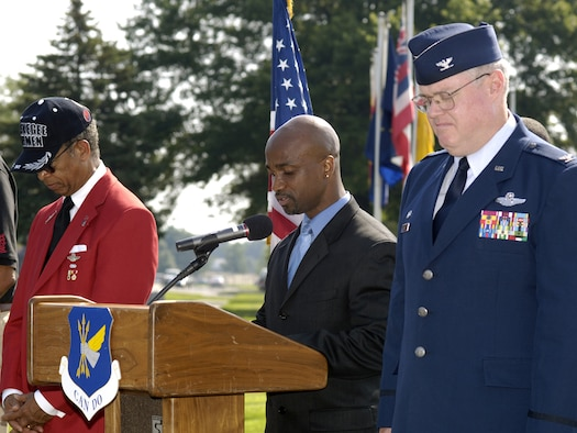 MCGUIRE AIR FORCE BASE, NJ - Col. James L. Kerr, 514th Air Mobility Wing Commander (right) stands on stage with Lt. Gen. (Ret) Russell Davis, Tuskegee Airmen, Inc. (left) while Titus Welcome, a civilian with 305 AWM (center) gives the invocation for the rededication ceremony of Tuskegee Airmen Avenue on McGuire Air Force Base. The ceremony was to recognize and honor the accomplishments and bravery of the Tuskegee Airmen in World War II. The ceremony was the first official event of the Tuskegee Airmen's 37th annual convention held in Philadelphia July 17 to 20. Col. Kerr opened the ceremony with his remarks and  Lt. Gen. (Ret) Davis gave the keynote speech. Afterwards they assisted with the unveiling of a new street sign featuring the Congressional Gold Medal in recognition of the Tuskegee Airmen's award received in March 2007. Tuskegee Airmen, Incorporated is a national organization that works to honor the accomplishments and perpetuate the history of the enlisted African-American men who enlisted during World War II to become America's first black military Airmen, ground crew and mechanics. They succeeded in their missions despite the challenges of racial discrimination. (U.S. Air Force Photo/ Mr. Kenneth Mann)
