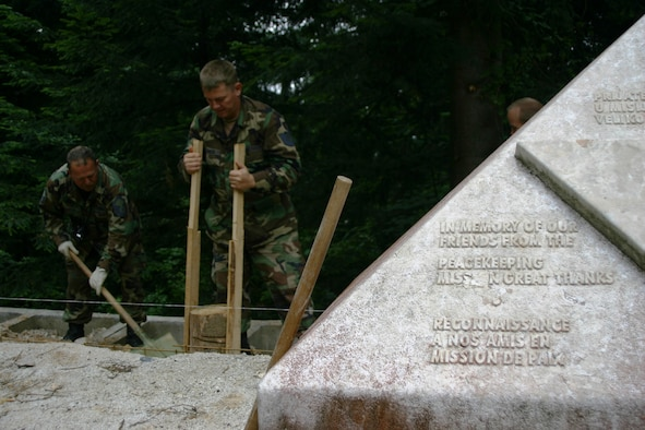 Master Sgt. Robert A. Gordon and Tech. Sgt. Shaun Blische, both members of the 175th Civil Engineer Squadron, restore a monument at Mount Igman, Bosnia-Herzegovina. The monument memorializes three American diplomats and their French driver, who were killed at the site in 1995. The memorial is being restored by members of the Maryland National Guard as part of a humanitarian civic action project under the auspices of the National Guard's State Partnership Program. (U.S. Air Force photo by Tech. Sgt. David D. Speicher)