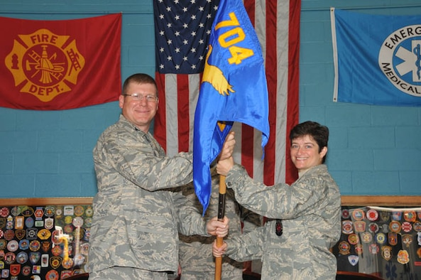 Col. Robert Bender, commander of the 704th Mission Support Group at Arnold Engineering Development Center (AEDC), hands the command flag to the new 704th Civil Engineering Squadron Commander Lt. Col. Saroya Follender. As squadron commander, she will be responsible for 24 government personnel and oversight of more than 400 contractors providing emergency and environmental services; housing and real property management and planning, programming, design and execution maintaining $7.8 billion infrastructure.   Prior to coming to AEDC, Colonel Follender was the commander, operations flight 314th Civil Engineer Squadron at Little Rock AFB, Ark. She led 195 military and civilian technicians and engineers in the maintenance, repair and minor construction.   She earned her Bachelor of Science degree in electrical engineering from Tufts University in Medford, Mass. She entered the Air Force in January 1991 through ROTC after graduation from Tufts. In 1995, she earned a Master of Science degree in engineering and environmental management for the Air Force Institute of Technology. She graduated from the College of Naval Command and Staff with a Master of Arts degree in national security and strategic studies.