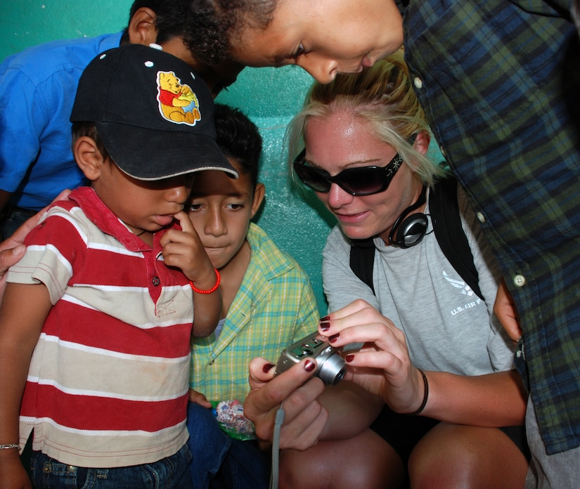Air Force Senior Airman Ashley Gordon, a weather forecaster with the 612th Air Base Squadron, shows children in Mira Valle village their photos on a digital camera. Military members and civilians from JTF-Bravo packed in nearly 1,600 pounds of food to the village July 26. (U.S. Air Force photo by Tech. Sgt. John Asselin)